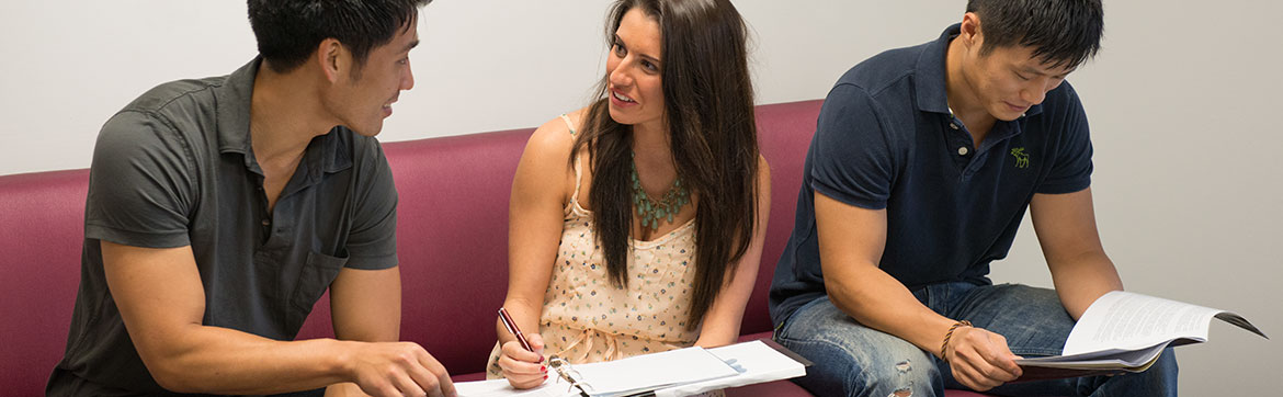 Image of a woman holding a notebook talking to a man