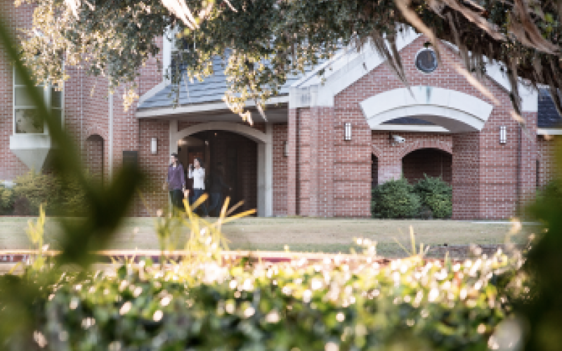 View of Dedman building and students walking on the grass