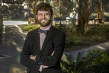 Image of Boebinger smiling with arms crossed on campus