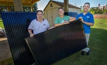 Three FSU alumni holding a solar panel
